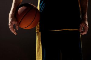 Silhouette view of a basketball player holding basket ball on